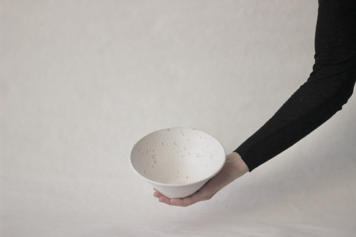 a hand holds white recycled studio clay bowl on a gray background