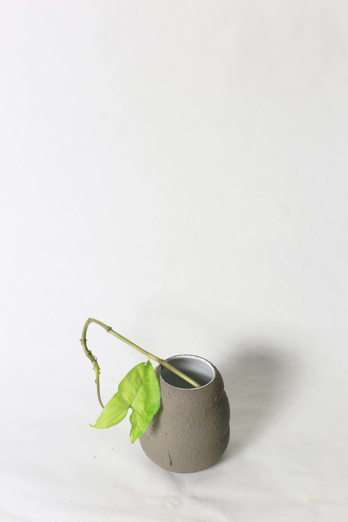 Graphite color ceramic vase in honey pot shape with green leaf on a white background over view 1