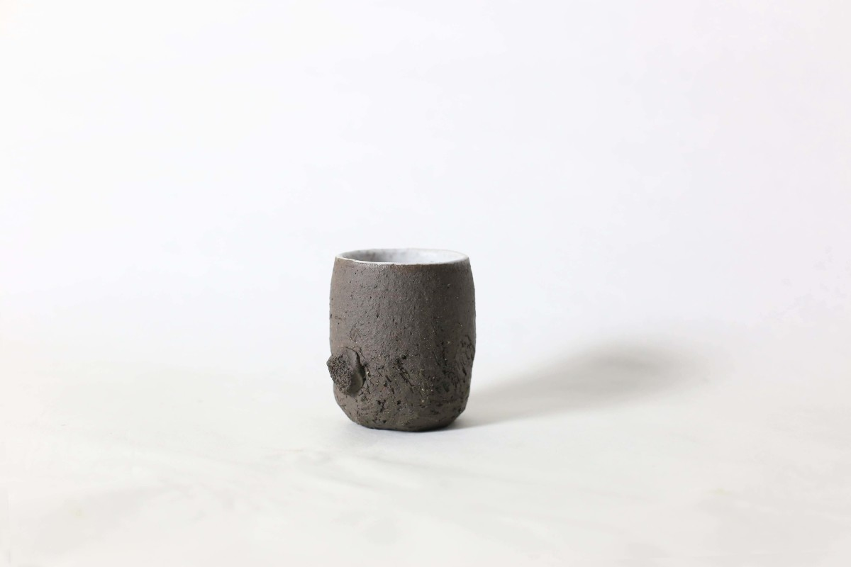 terra nigra clay cup with a lump below on a white background close shot