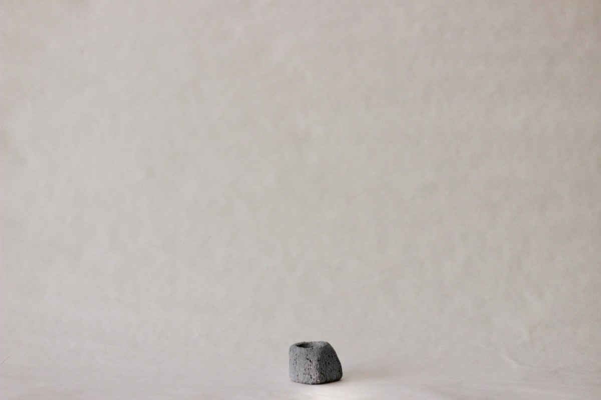 small gray ceramic candle holder on a gray background