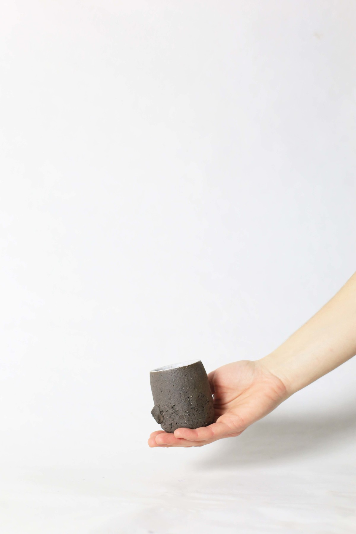 a hand holds terra nigra clay cup with a bulge below on a white background
