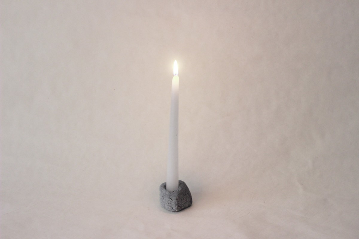 small gray ceramic candle holder with lighted candle on a gray background 1
