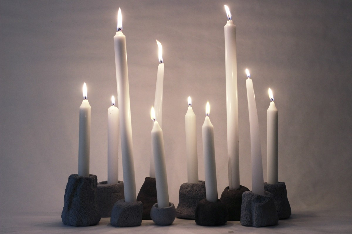 eleven ceramic candle holders with lighted candles on a gray background