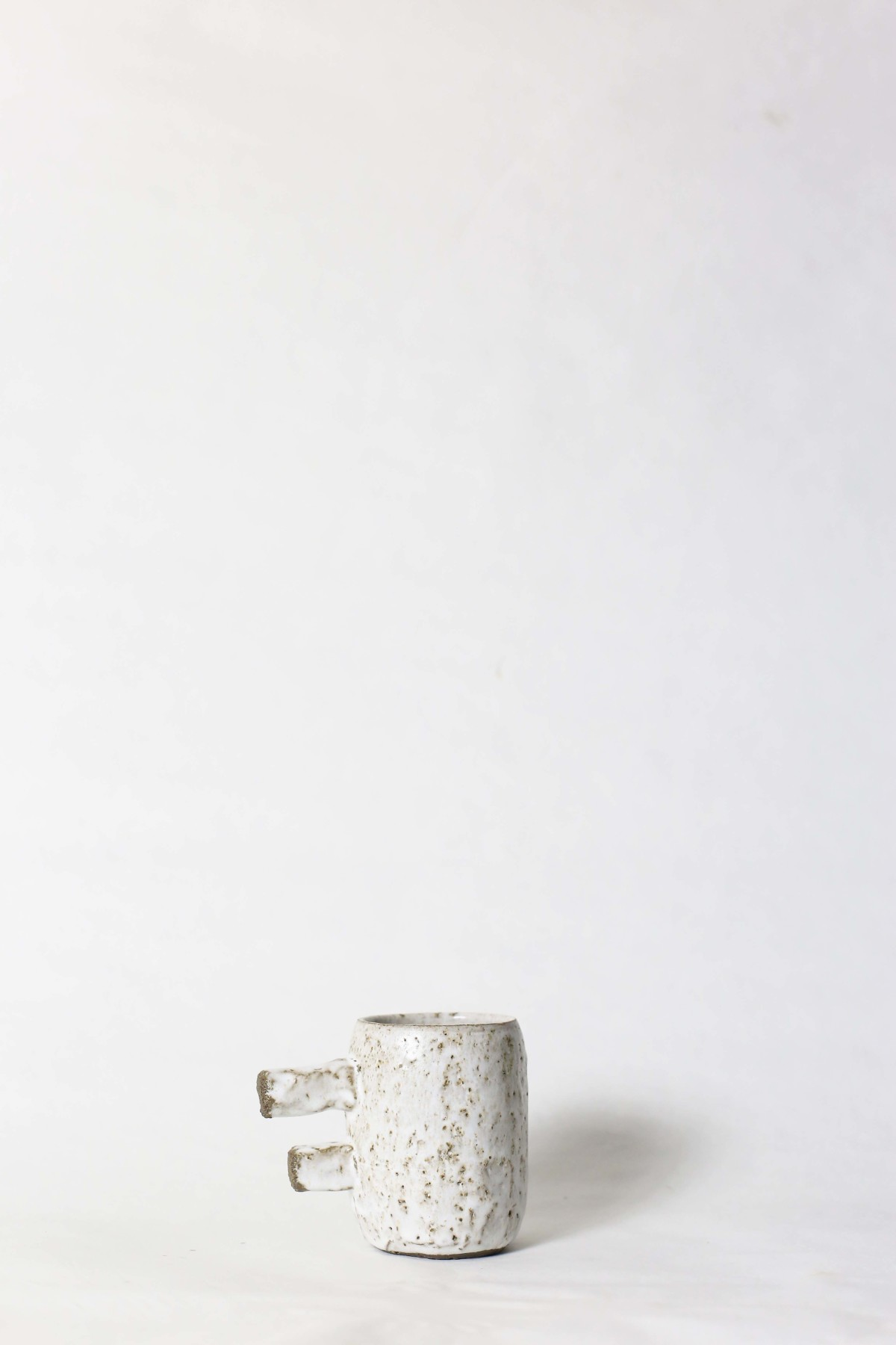 spotty white ceramic cup with two stick handle on a white background 1