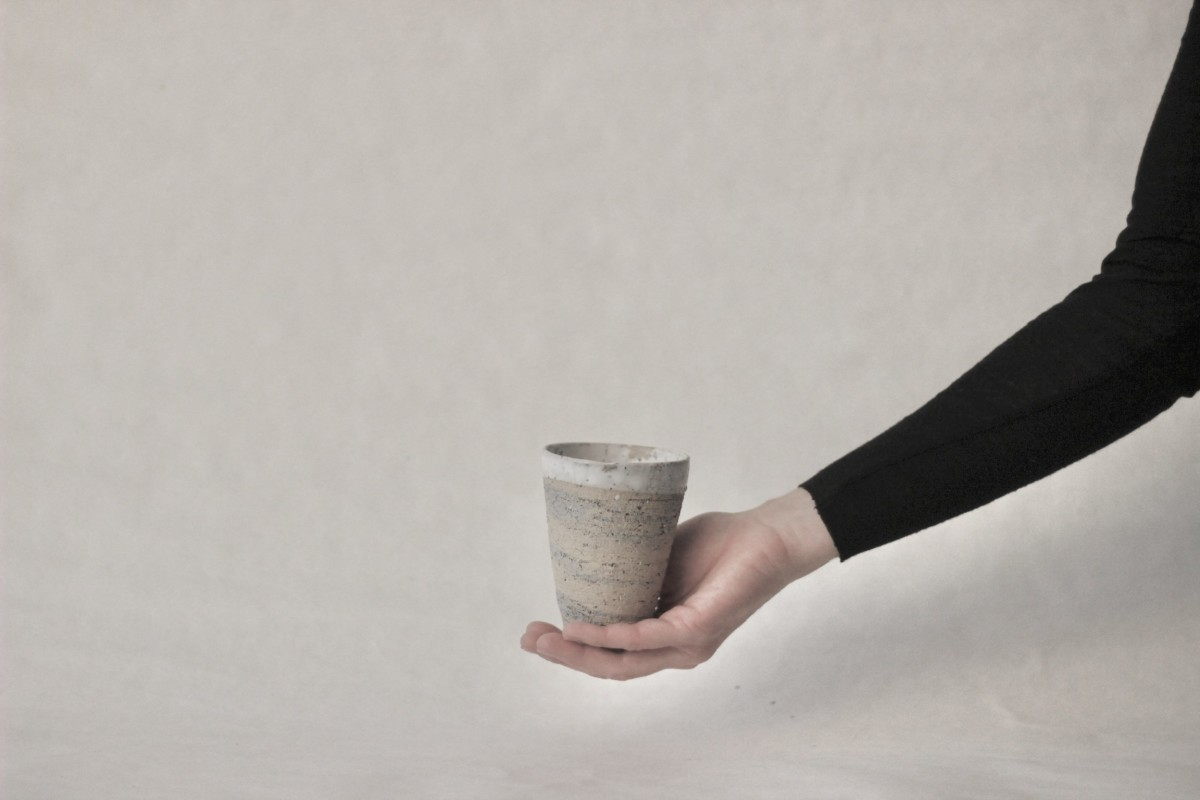 a hand holds mixed recycled clay cup on a gray background