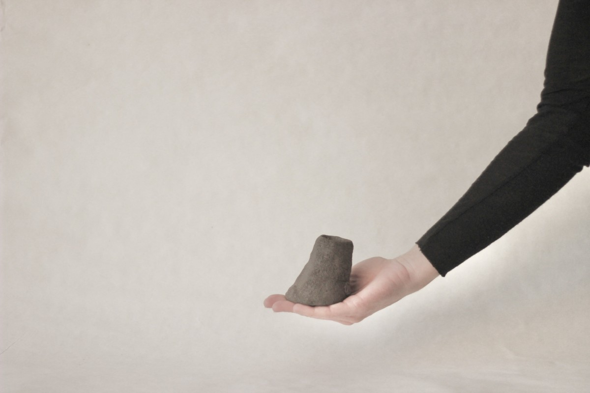 a hand holds brown ceramic candle holder on a gray background