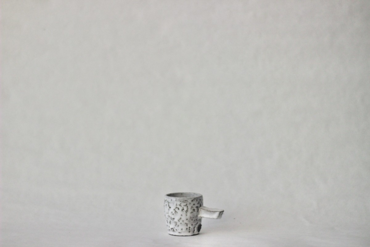gray spotty ceramic coffee cup on a gray background 2