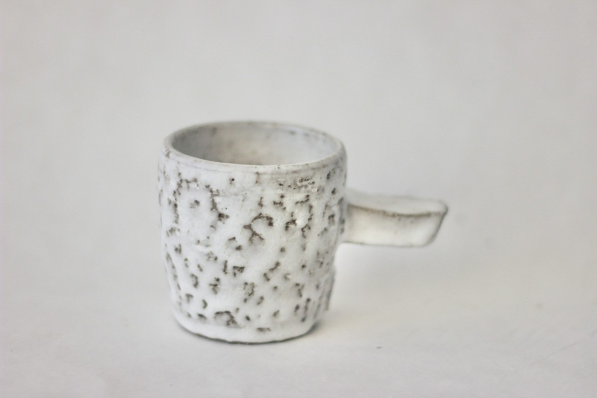gray spotty ceramic coffee cup on a gray background close shot