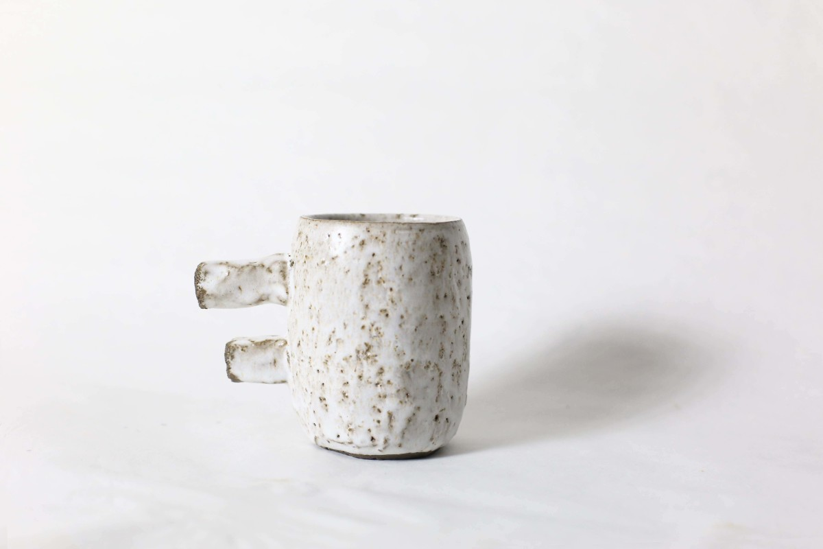spotty white ceramic cup with two stick handle on a white background close shot