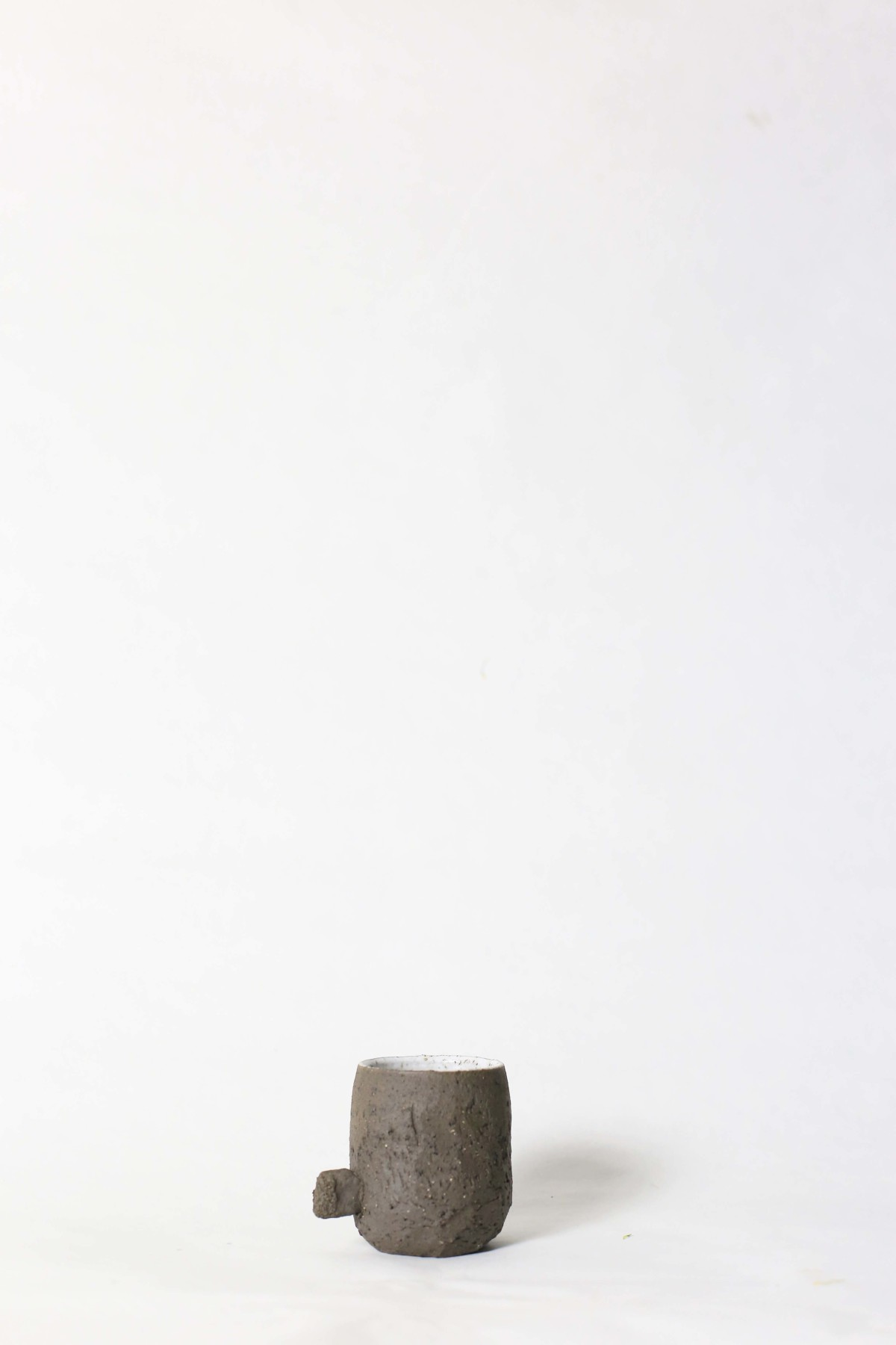 Terra nigra clay cup with a knot below on a white background