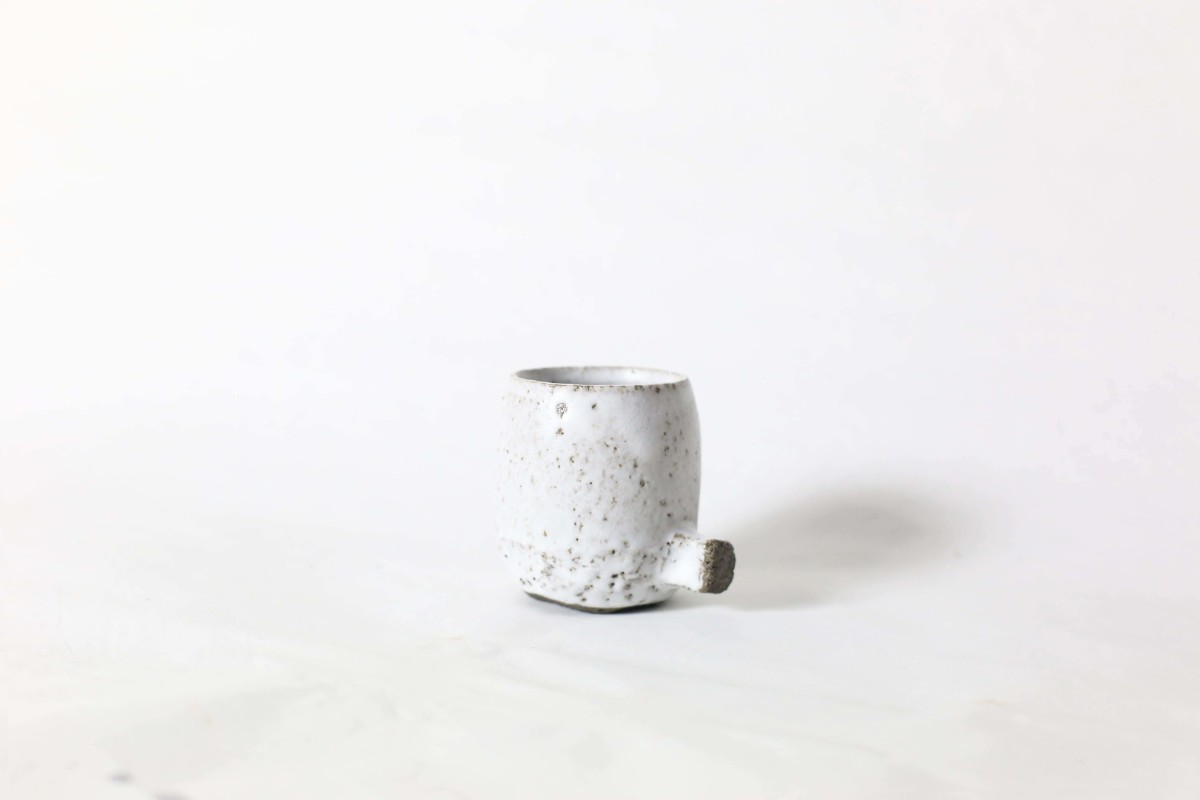 White ceramic cup with knot below on a white background close shot