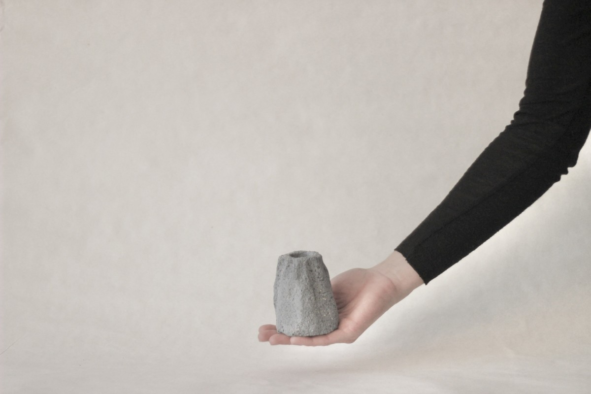a hand holds gray ceramic candle holder on gray background