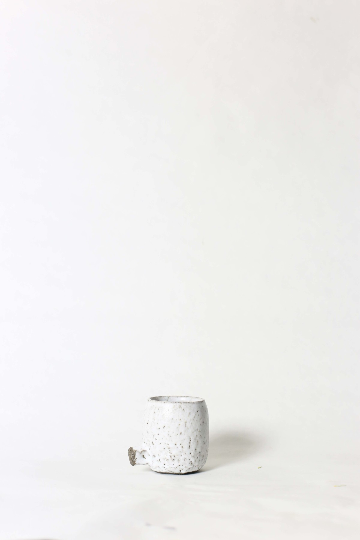 White ceramic cup with knot below on a white background 1