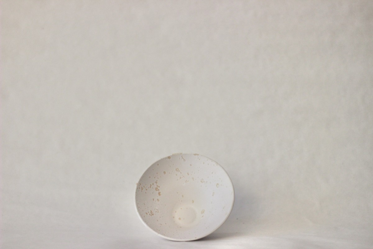 white recycled studio clay bowl on a gray background on the side
