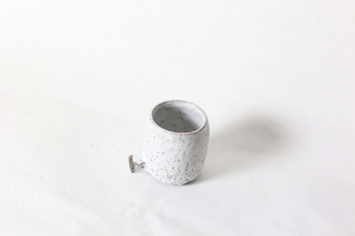 White ceramic cup with knot below on a white background over view
