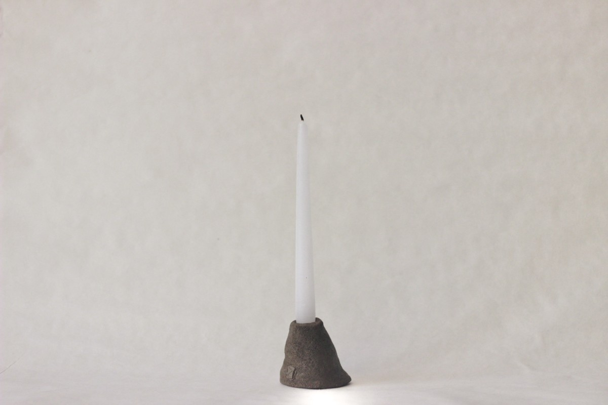 brown ceramic candle holder with white candle on a gray background 1