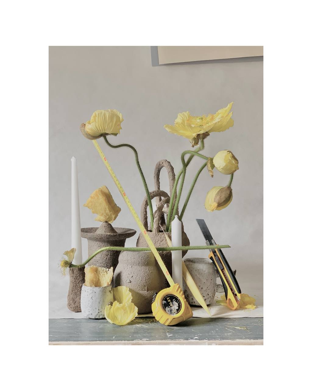 Still life of gray ceramic vases and different yellow objects