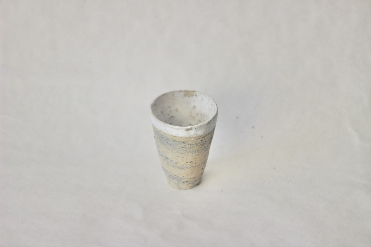 Mixed recycled clay cup on a gray background