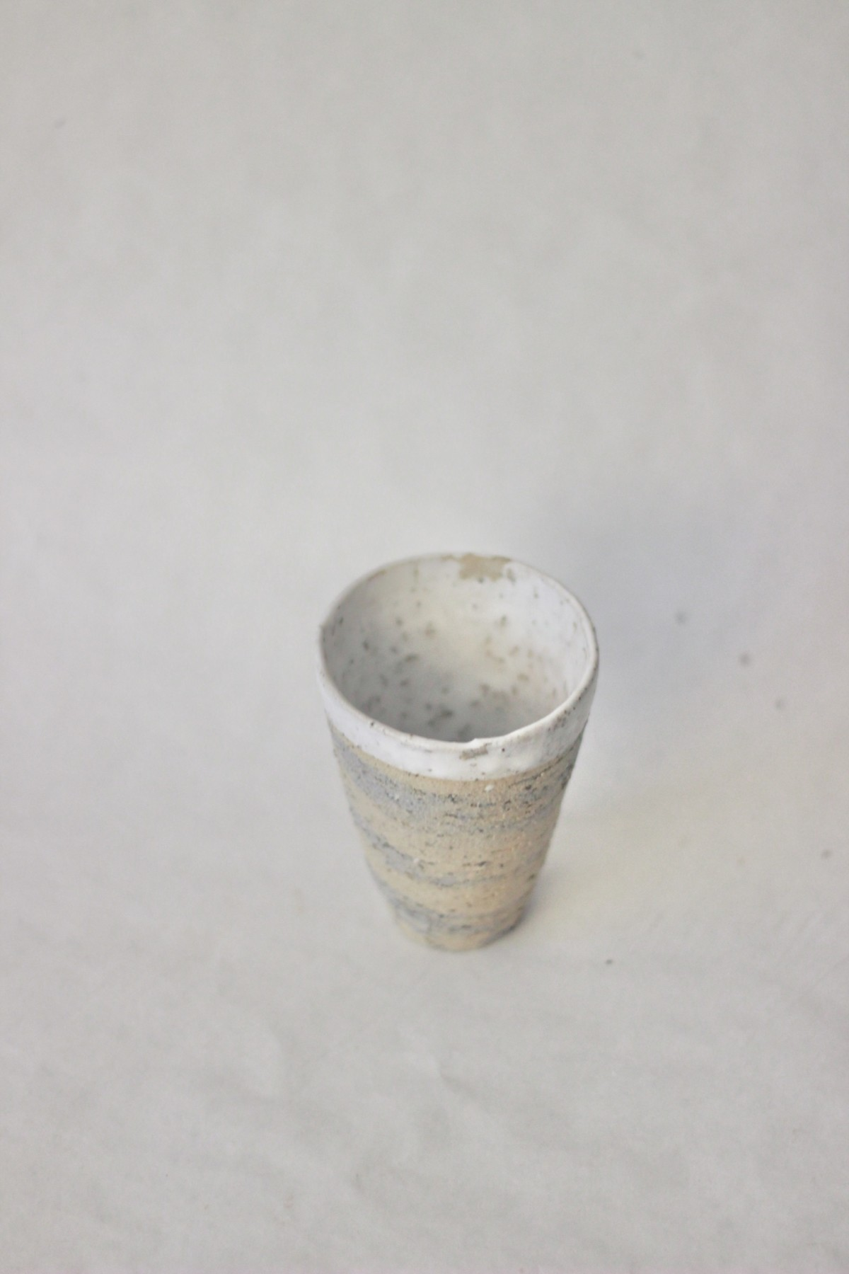 Mixed recycled clay cup on a gray background over view I