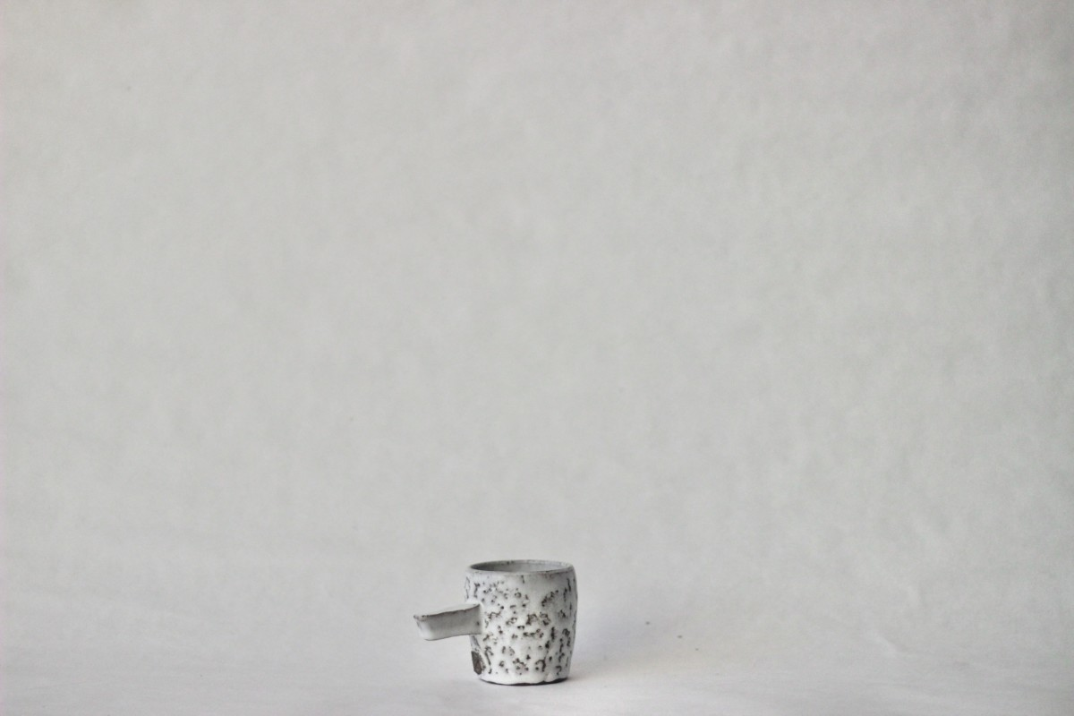 gray spotty ceramic coffee cup on a gray background