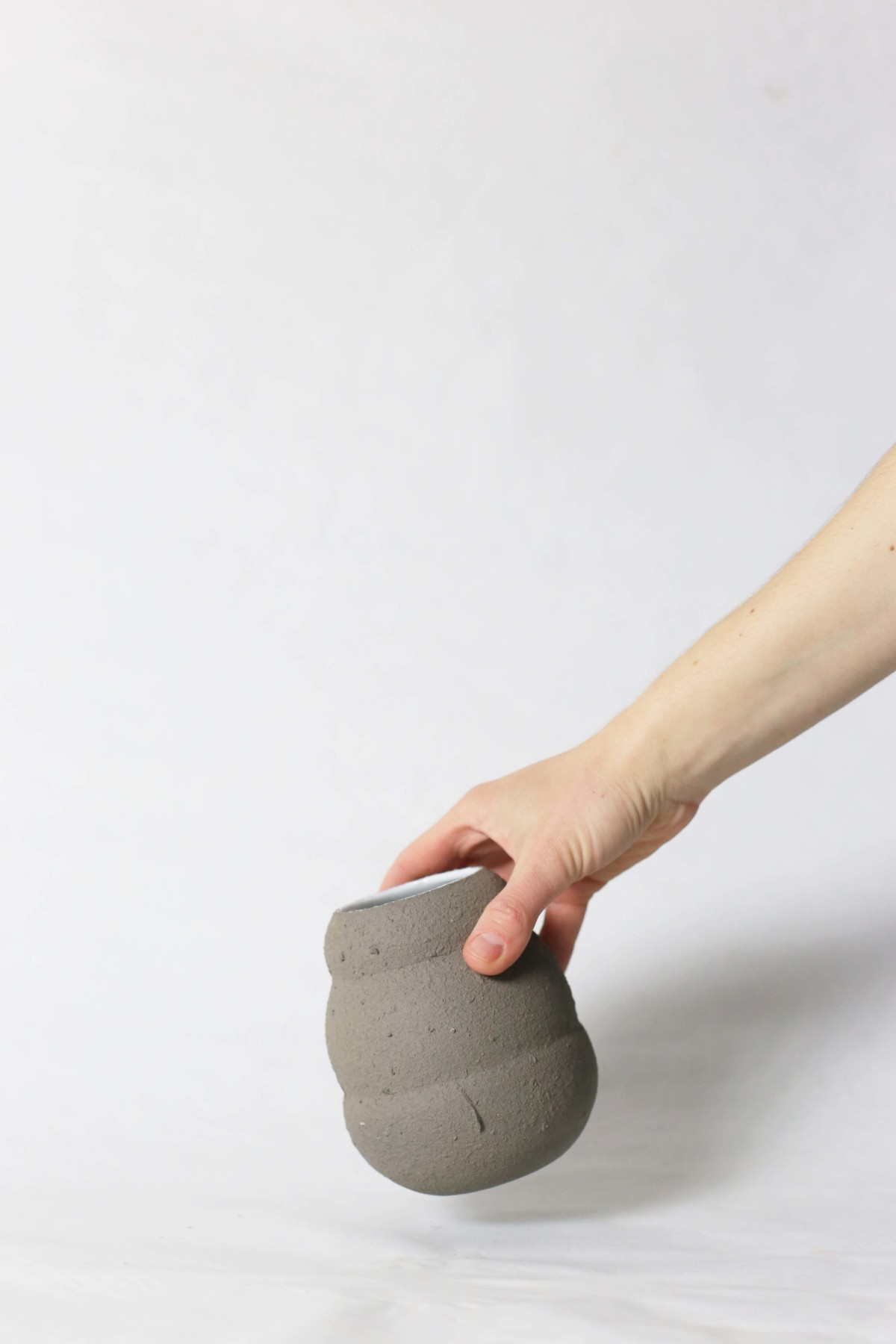 A hand holds graphite color ceramic vase in honey pot shape on a white background