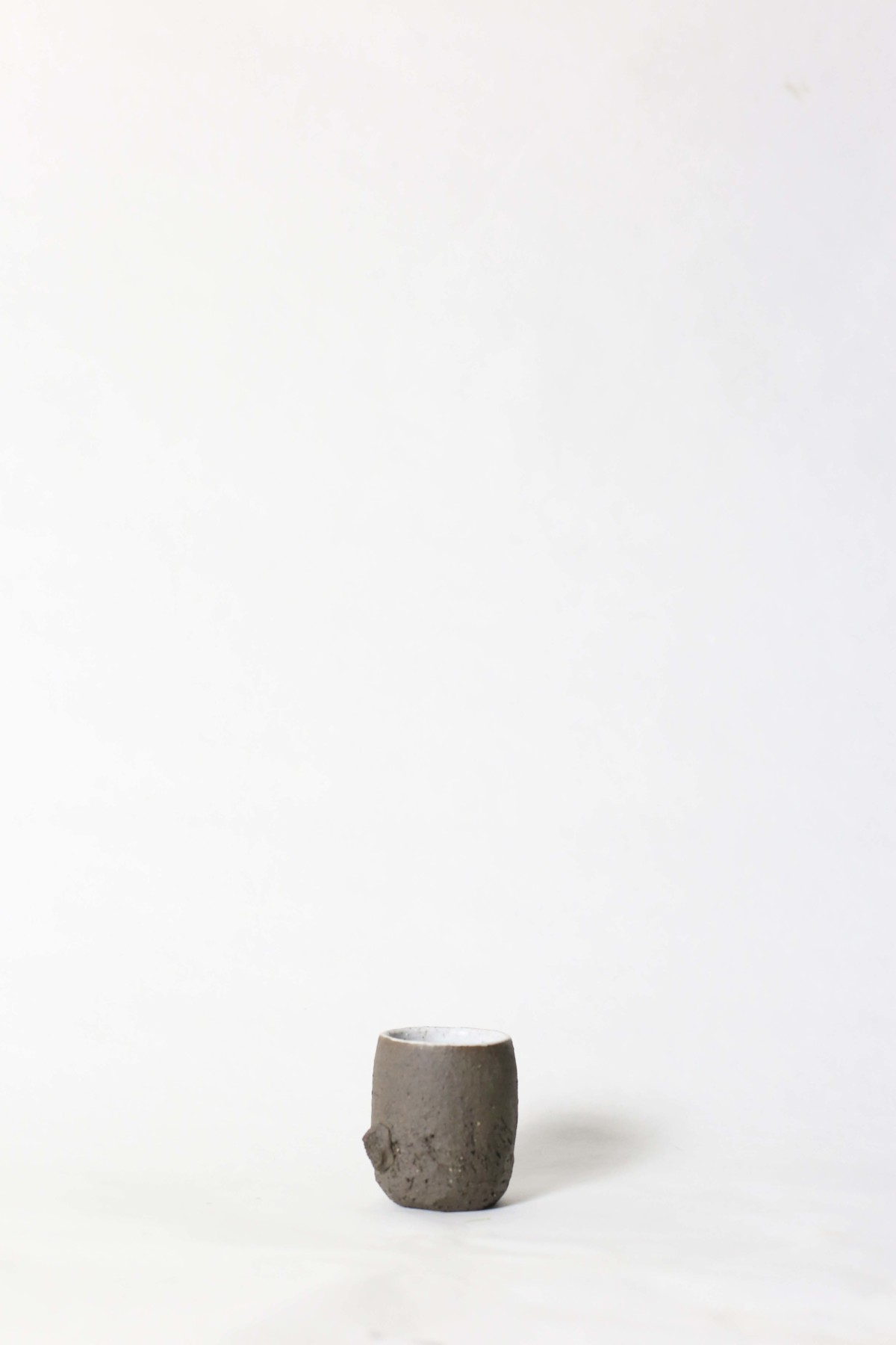 terra nigra clay cup with a lump below on a white background 1