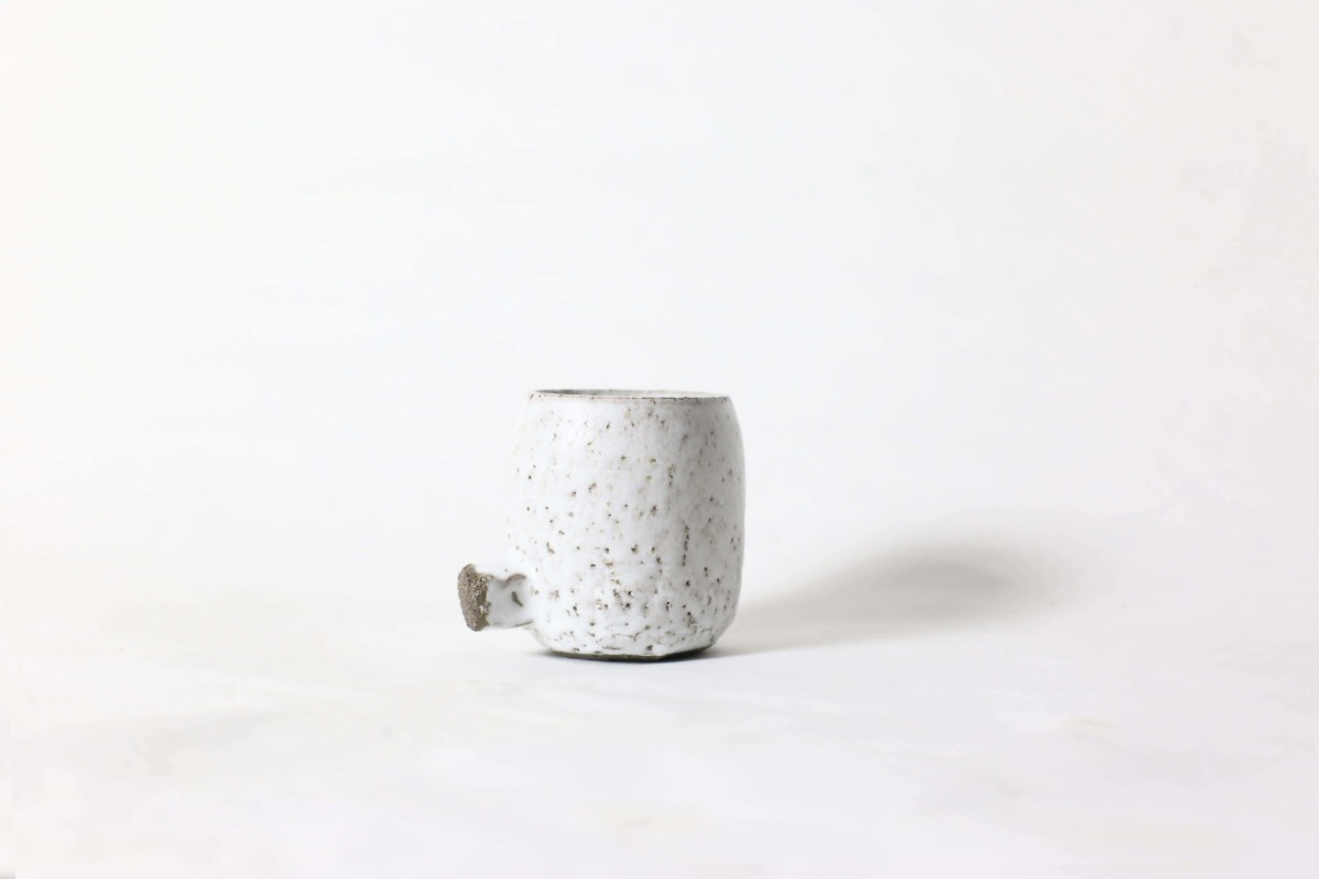 White ceramic cup with knot below on a white background close shot 2