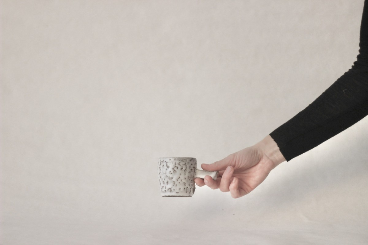 a hand holds gray spotty ceramic coffee cup on a gray background