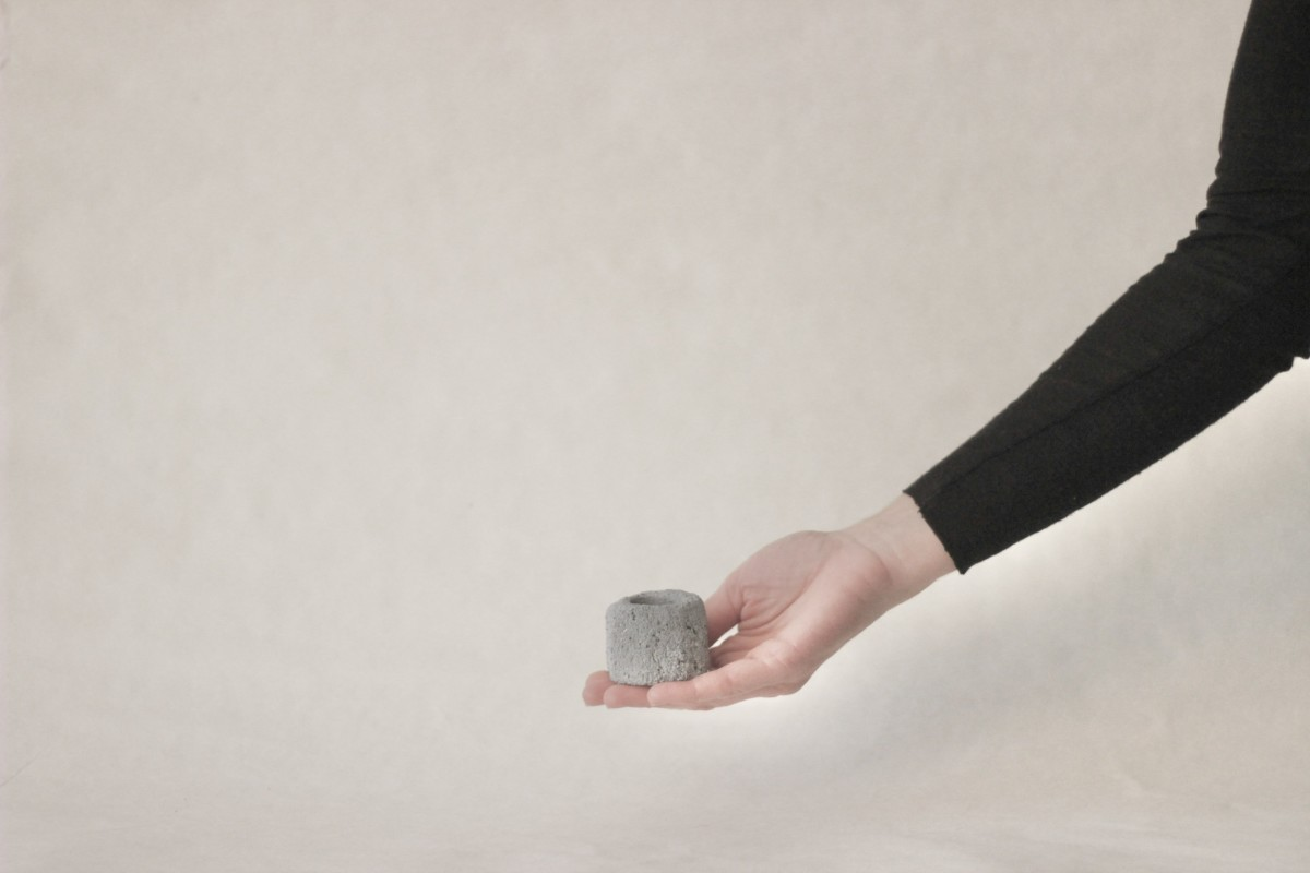 a hand holds small gray ceramic candle holder on a gray background