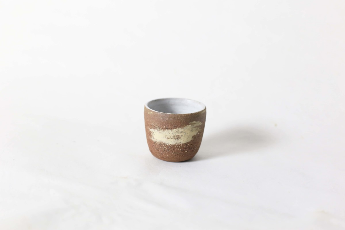 terracotta and sand color clay cup on a white background close shot 1