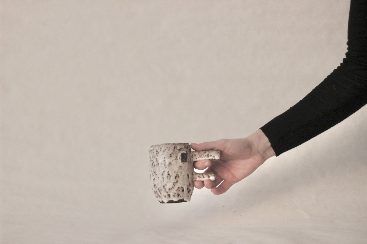 a hand holds spotty ceramic mug on a white background