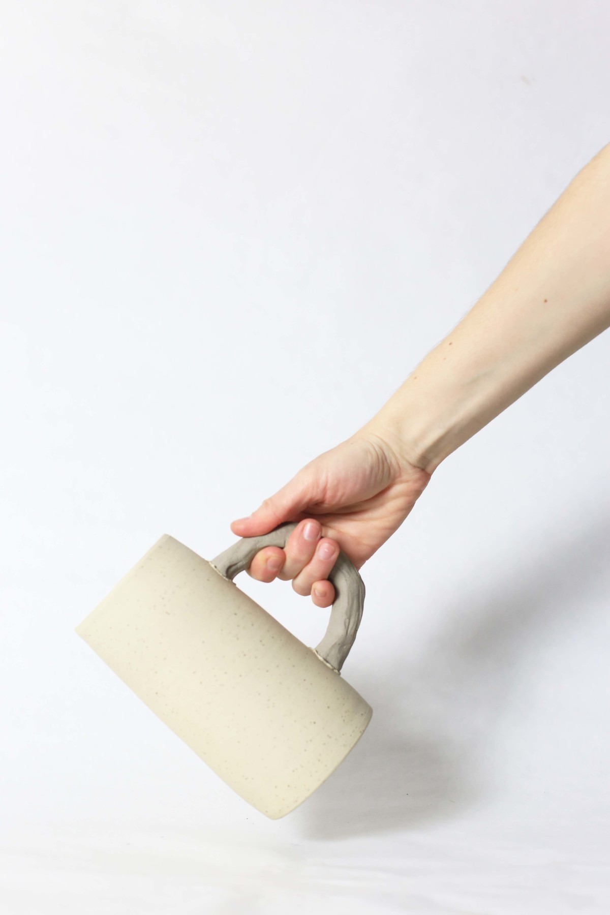 A hand holds beige ceramic jug on a white background over view