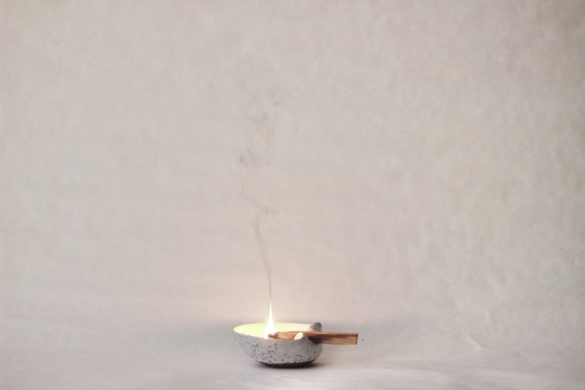 ceramic white palo santo bowl with lighted palo santo on a white background
