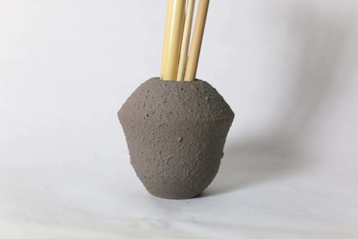 Small grey ceramic vase with brushes in it on a white background close shot