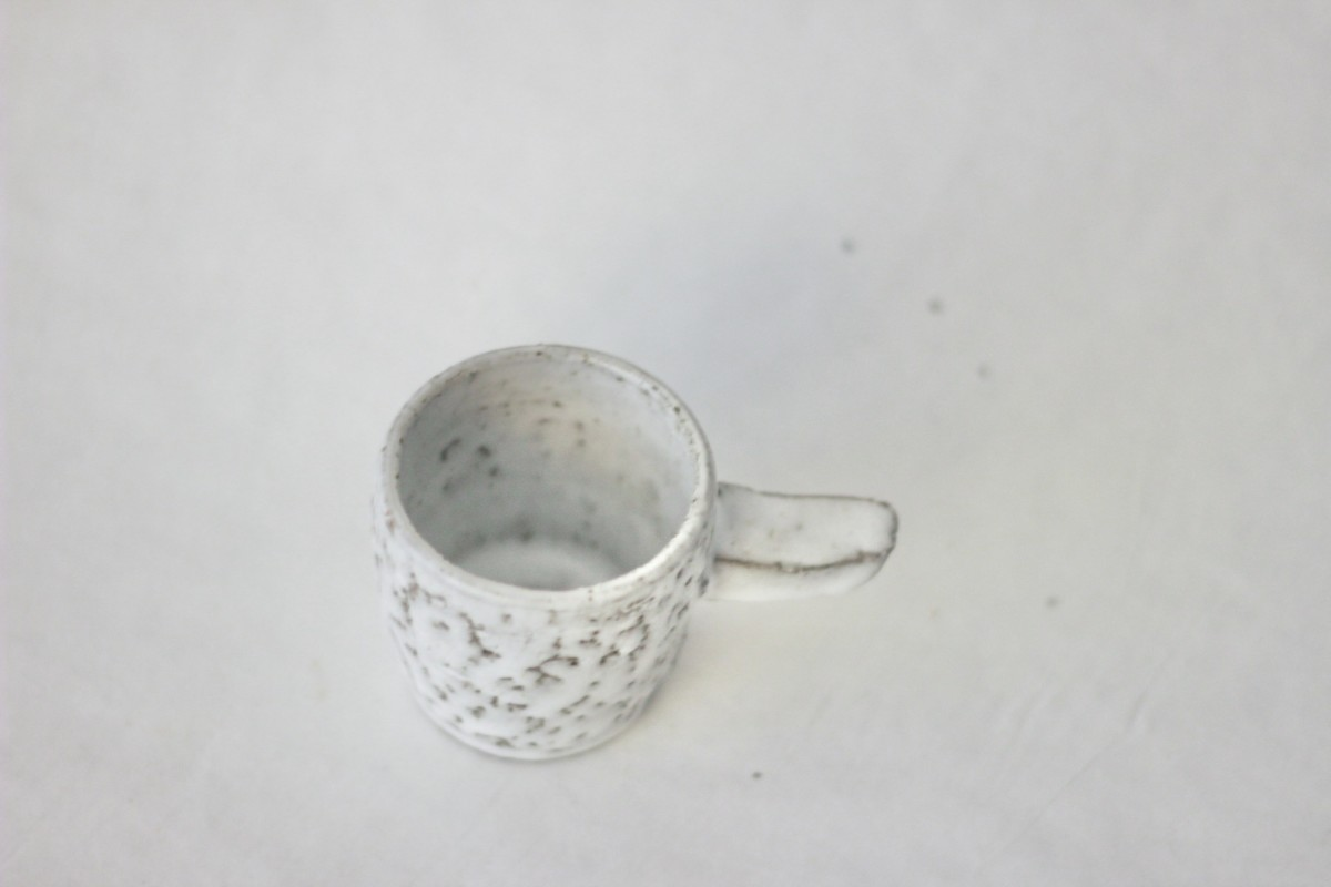 gray spotty ceramic coffee cup on a gray background over view