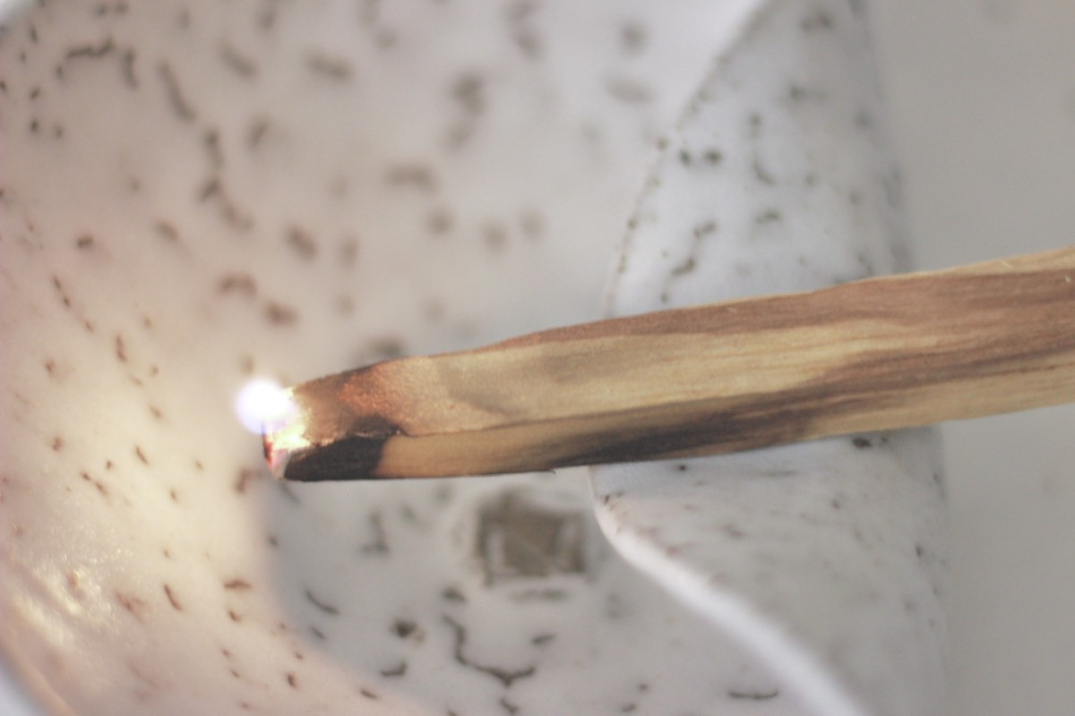 ceramic white palo santo holder with lighted palo santo on a white background close shot 1
