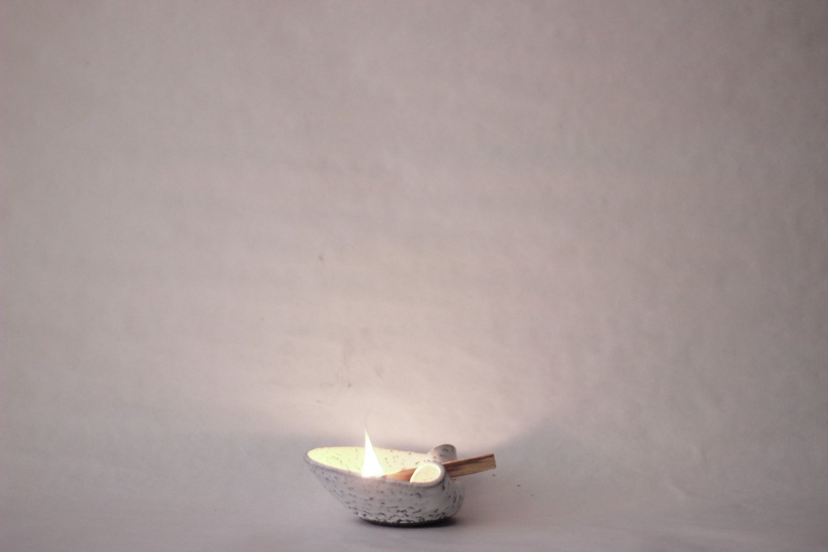 ceramic white palo santo holder with lighted palo santo on a white background