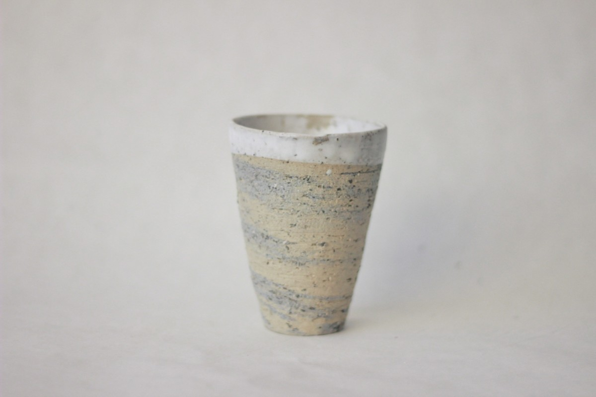 Mixed recycled clay cup on a gray background close shot