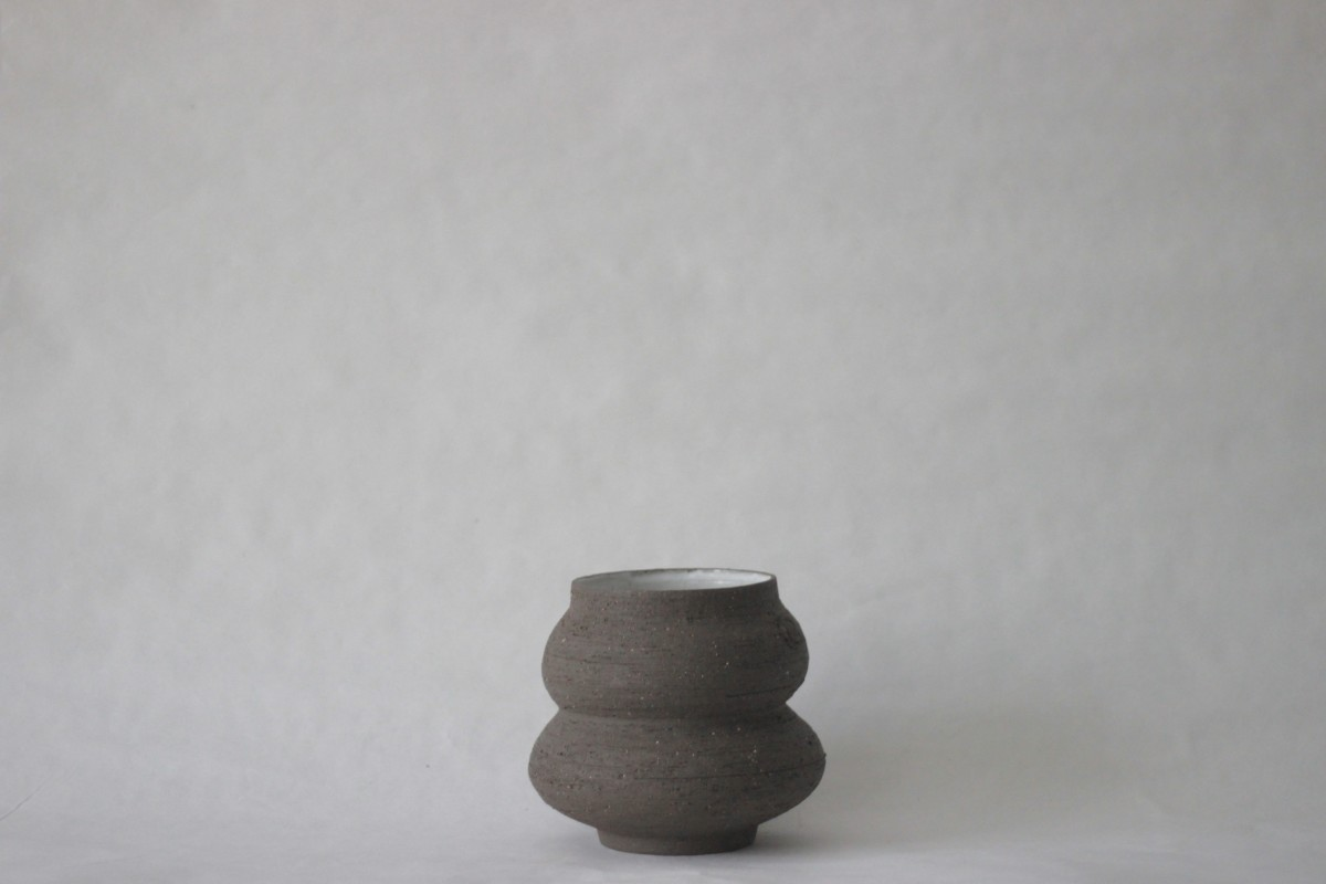 wide neck brown ceramic vase on a white background