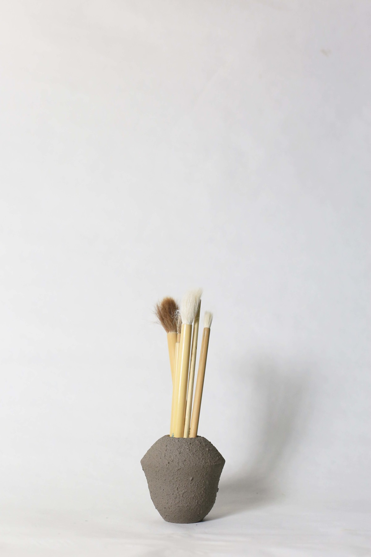 Small grey ceramic vase with brushes in it on a white background