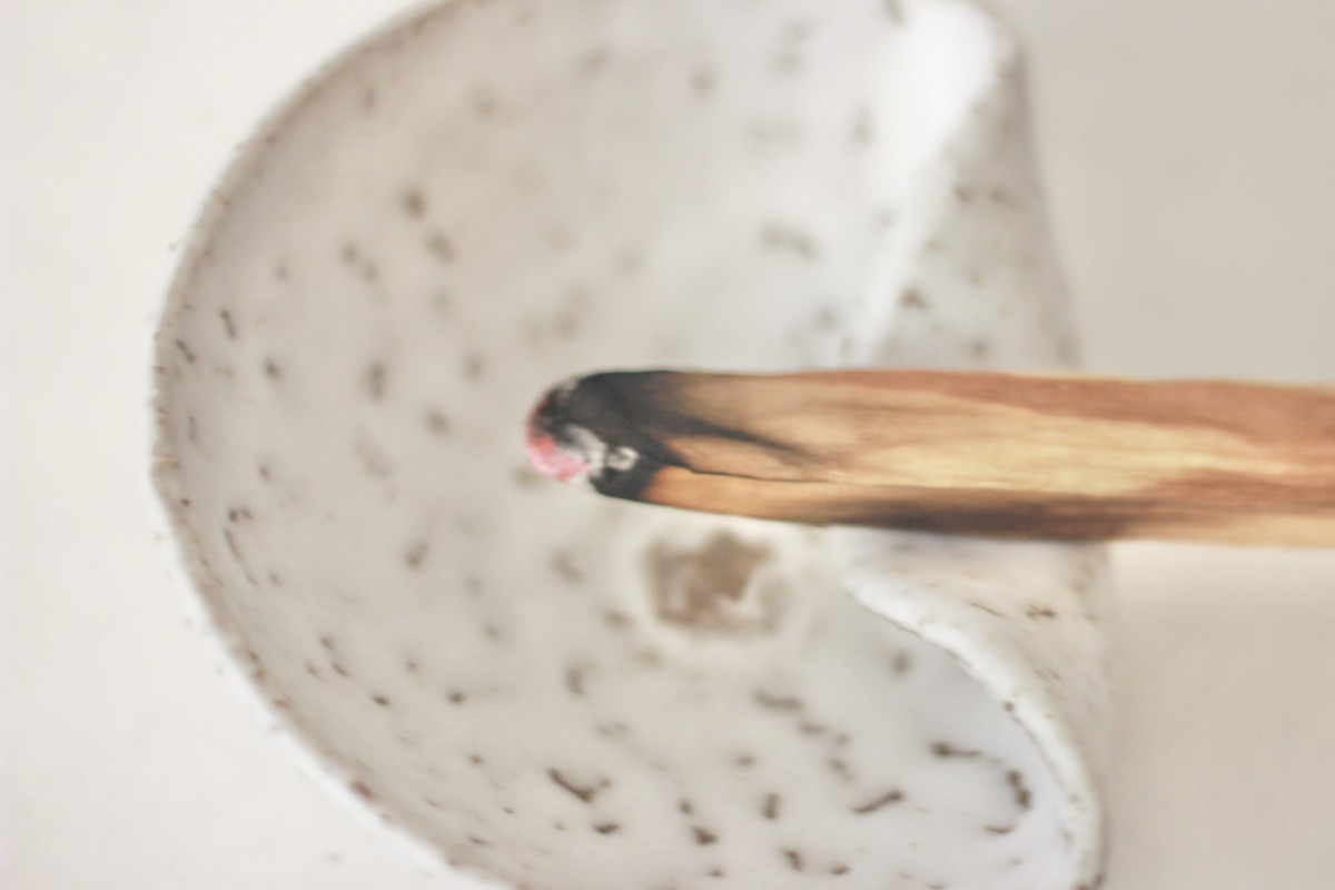 ceramic white palo santo bowl with lighted palo santo on a white background close shot 1