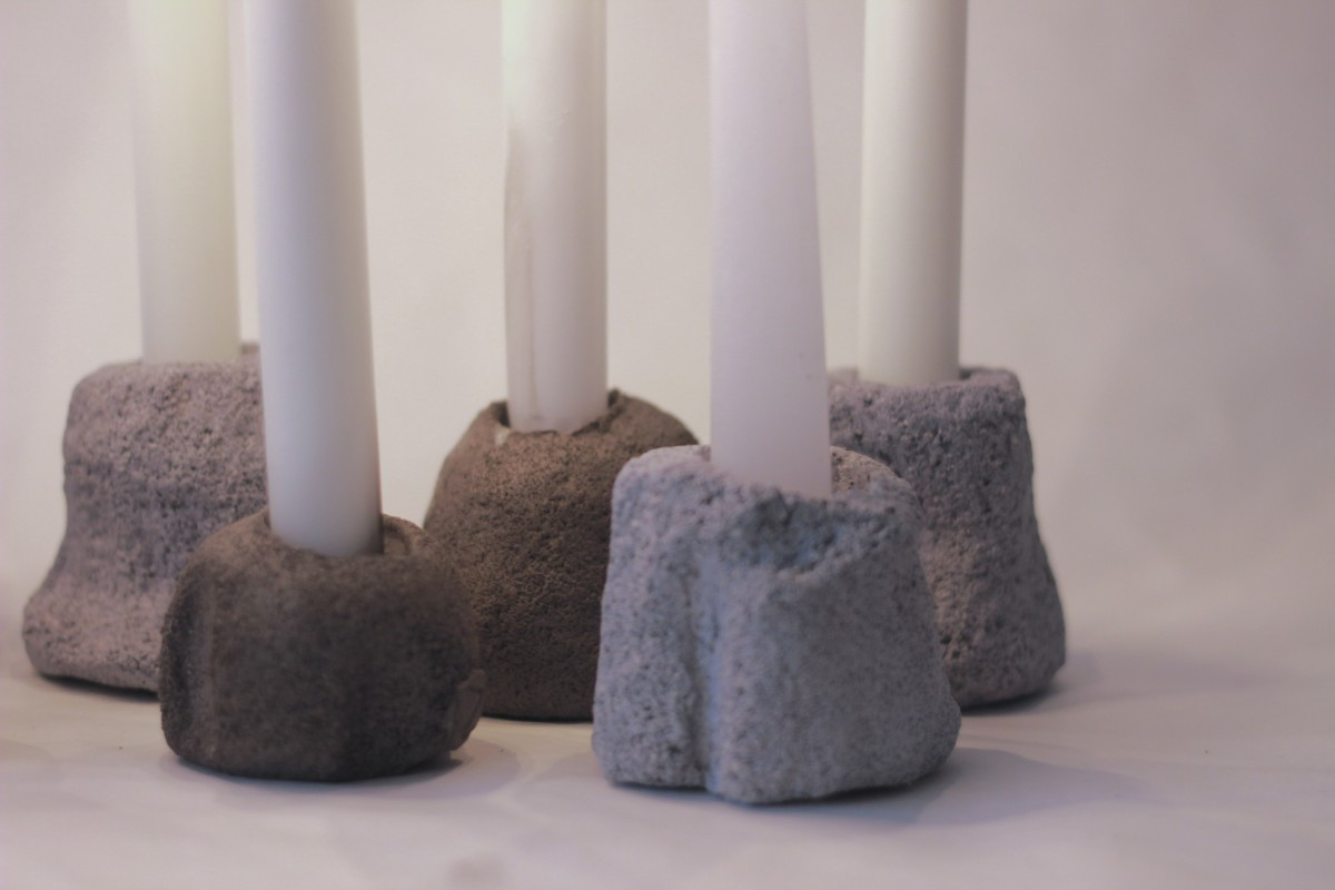 five ceramic candleholders with lighted candle on a white background