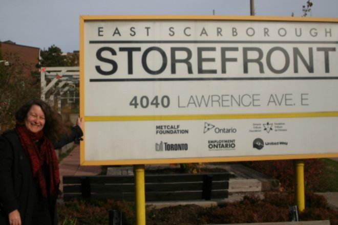 Woman in front of East Scarborough Storefront sign