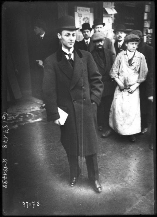 black and white photograph of a man in suit, coat and bowler hst