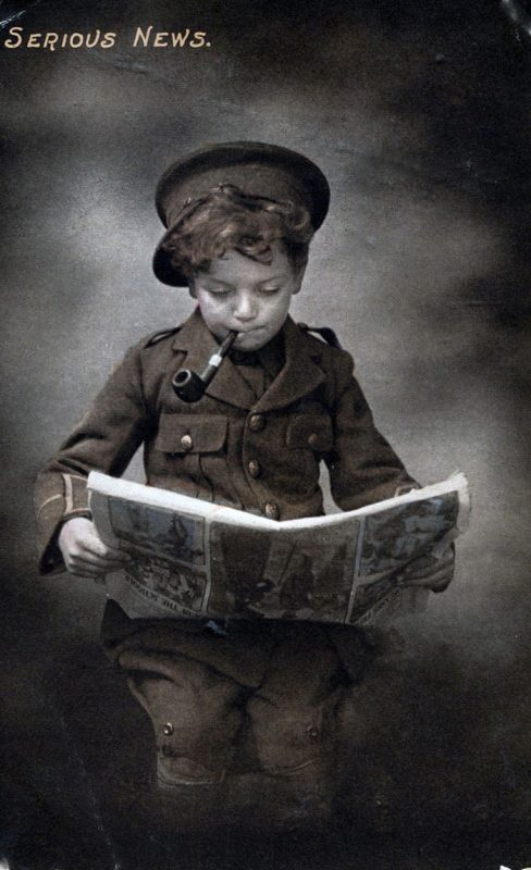 boy in military uniform reading a newspaper