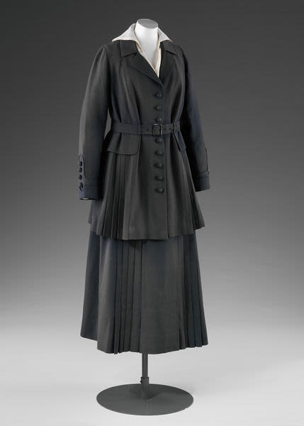 A coloured tailored jacket and skirt in dark grey wool serge displayed on a mannequin