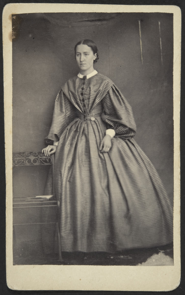 black and white photograph, a full-length portrait of a woman who stands by a chair and is wearing a long dress