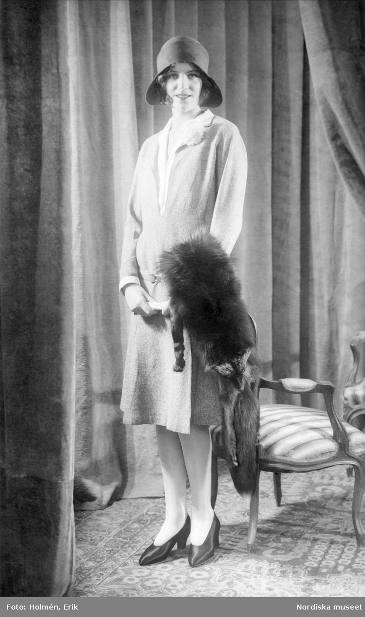 black-and-white photograph of a model in a hat and a wool dress, a stuffed fox scarf draped over her arm.