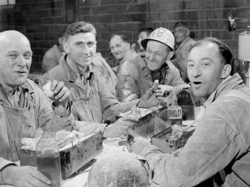 four smiling men in workwear sit together eating