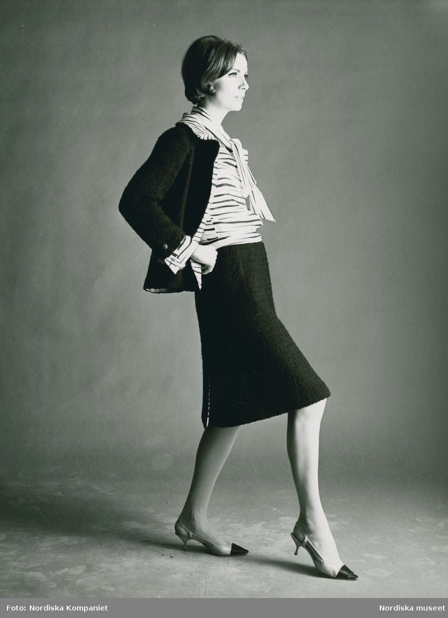 Person posing in a in dark suit and striped tie blouse, wearing heels